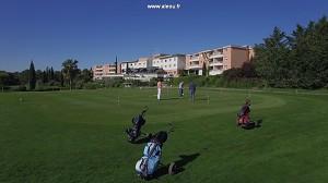Vista aérea de golf, fuente y hotel de calidad.